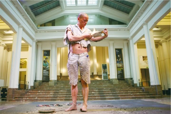 《涅槃•肉身》行为作品,2013年4月13日16:45-4月14日16:45,比利时布鲁塞尔国家美术馆  何云昌把身上的所有衣服一点一点全部烧尽,历时24小时