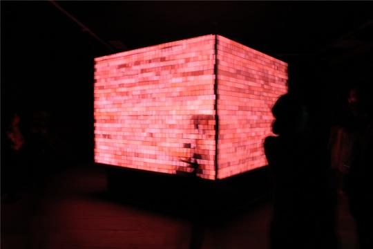 作品的选择涵盖上世纪五、六十年代至今的声音作品,包括具体声音创始人Pierre Schaeffer的三件文献性作品。区别于常规架上绘画或三维作品,声音装置作品强调现场参与感,展厅的光线大多昏暗,电子设备很难拍摄出完美的照片。《声音立方体》的展厅变身录音室,馆方重新做了天花板,麦克放置于屋顶顶部采集展厅内观众与作品互动时发出的声音,整个空间如同一个魔方世界,漆黑的展厅中立体的屏幕各个平面随着场内观众发出声音的强度变换出不同颜色、屏幕上元素的疏密度也相应变化。《建筑声音》是本次展览中唯一一位女艺术家的作品,它