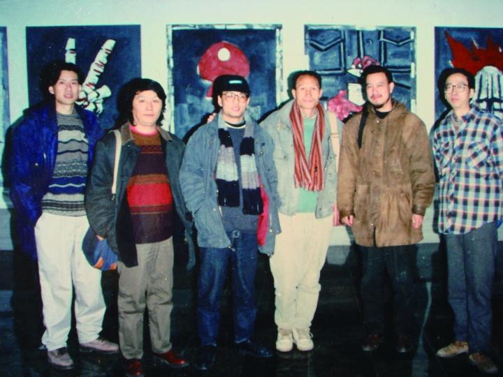 """《九十年代的中国美术:""""中国经验""""画展》主持人与参展艺术家在展厅毛旭辉画前合影"""