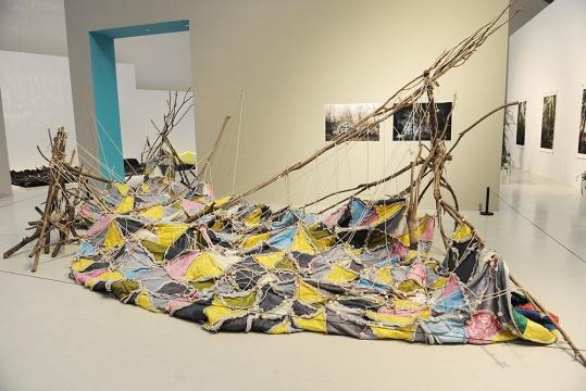 来自广东时代美术馆推荐,80后艺术家张新军创作的装置作品《树林睡袋树林》,张扬的树枝与拼接的睡袋,又一次满足了艺术家想要做的好玩的心理需求,虽然它并不容易