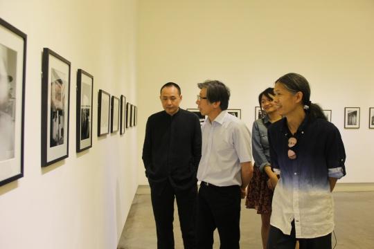 三影堂摄影艺术中心创始人荣荣(右一)与嘉宾中央美术学院院长范迪安(左二)观看展览