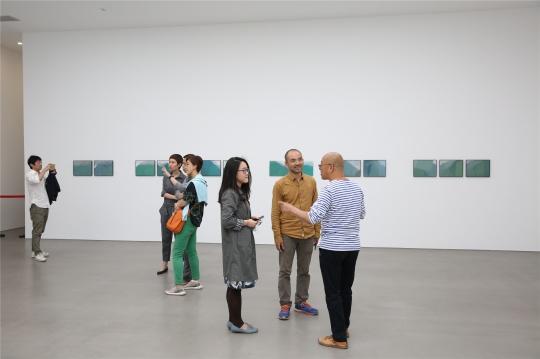 艺术家郭海强(黄色服装)在现场给来宾讲解作品