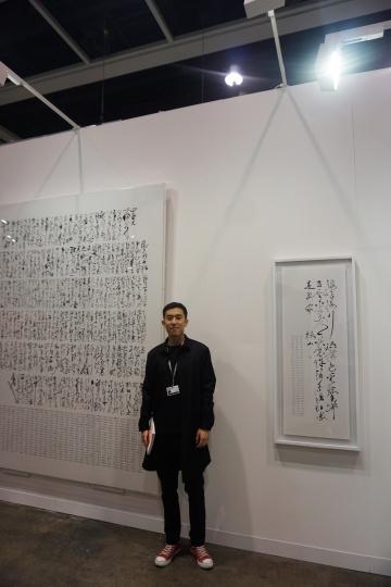 艺术家李舜在其两件作品前,他身后的两件作品均已成交,分别售价11万元、6万元人民币