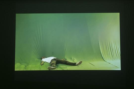 """辛云鹏《20140828》,由一声枪响,演员应声倒地开始,作者通过固定镜头记录下长达二十多分钟的""""假死""""。作为导演,在拍摄过程中作者并没有给予演员任何停止的口令,以致于躺在地上的演员在等待中睡着。"""
