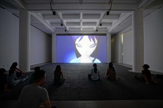 """""""菲利普·帕雷诺:共此时""""二楼展厅,观众坐在地毯上看影片《这世界以外的任何地方》"""