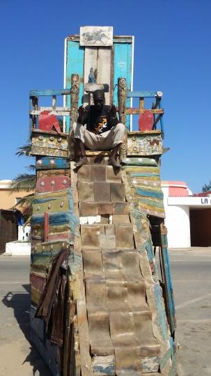 """刘冰在塞内加尔遇见的一个冈比亚人,他自称是艺术家。图中的高高的""""宝座""""是他自己手工制作的,在刘冰眼中,这位艺术家坐在""""宝座""""上,就像是一个帝王。后来他还送给了刘冰一条项链,也是刘冰至今佩戴在身上的"""