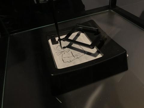 书写笔按照观众在ipad上画下图形在沙台上将其复制画下来