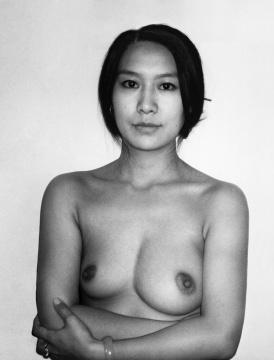 """董金玲 行为图片 100 × 80 cm 2012   2011年,董金玲的孩子出生,她决定将其中一个乳房不用于哺乳,让它不再为人类的繁衍工作。于是,她偏执地用左侧乳房哺乳,甚至不让孩子碰触到右侧乳房。由于产后哺乳期的乳汁淤滞,右侧乳房有着界线不清的硬块之后出现了乳腺组织的急性化脓性感染。三个月后右侧乳房已经不再分泌乳汁。左侧乳房由于乳腺的发育而过度膨胀,左右乳房的大小也愈发不同。这是一个精神与身体双重痛苦的过程,也饱含了艺术家最为复杂的情感与决心:对生育的欣喜与恐惧;对自己身份的审视,即她在世界中作为""""人""""的位置。作品中,乳房观念上的属性变了,视觉上也变了,她左侧的""""乳房""""不再是""""乳房"""",而是""""董金玲"""",一件其私藏的艺术品"""