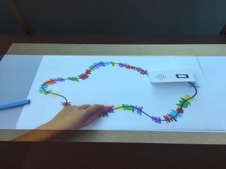 """铃木尤理 《追色者》 2013  """"追色者""""是一组沿着黑色线条移动的小型机器人,它们能够辨识观者画下的彩色线条,并将色彩转译为音乐,降低了初学者演奏和享受音乐的门槛"""