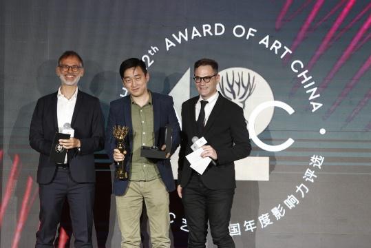 第12届AAC艺术中国评委马可·丹尼尔(左)、田霏宇(右)年度策展人得主冯博一(刘钢代领)