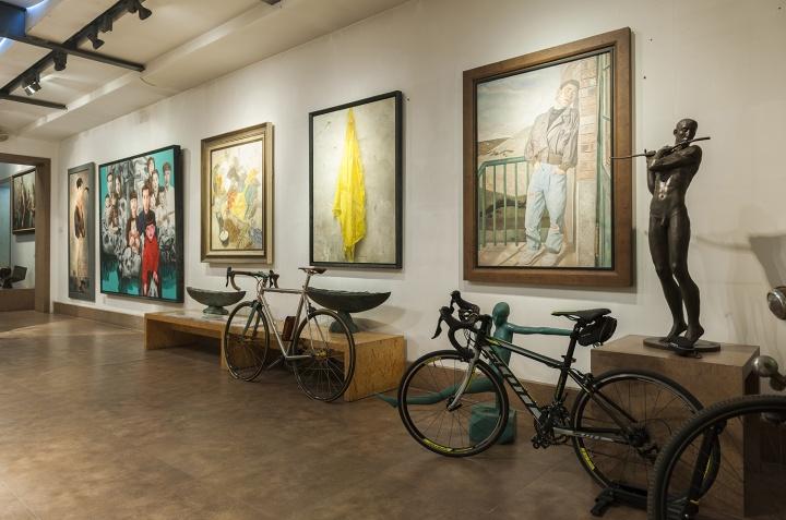 墙面上的作品(左起):毛焰《X的肖像》、喻红《繁衍》、曹力《平凡生活》、陈文骥《塑料雨衣》、石良《春日彩虹》,右侧雕塑为魏小明《笛声》(摄影:董林)