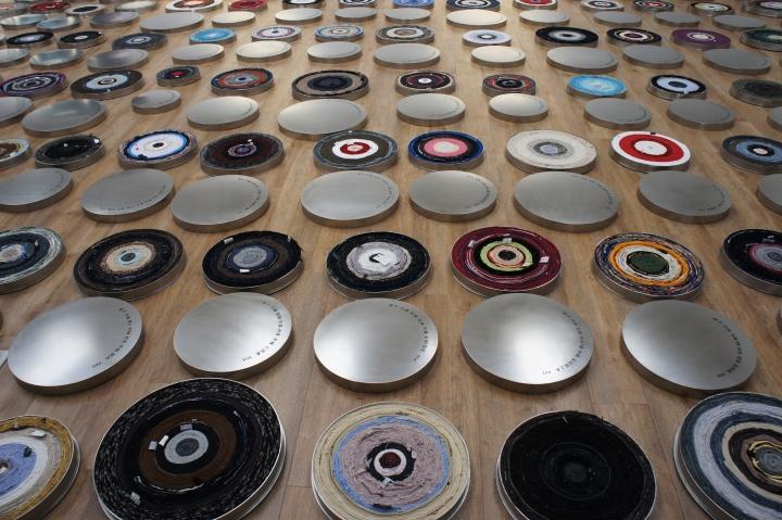 《一句话》装置  不同人穿过的衣服、不锈钢 2011 (横滨三年展) ,尹秀珍将108件个人的衣服拆开,再重新缠绕成电影胶卷一样的卷轴,放在摆放成螺旋形的圆盒中。