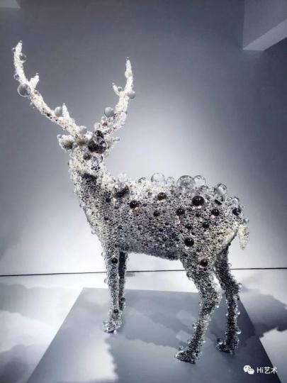 """《PixCell-Deer#41》205×155×70cm树脂、动物标本、玻璃珠、不锈钢2015 名和晃平使用玻璃珠、聚氨酯泡沫塑料、硅油以及大量不同技术和材料,以实现其原创概念 """"棱镜"""",并探索雕塑的潜能。他近期的项目将此种探索延伸至建筑和行为艺术,达成空间和艺术的融合呈现。"""