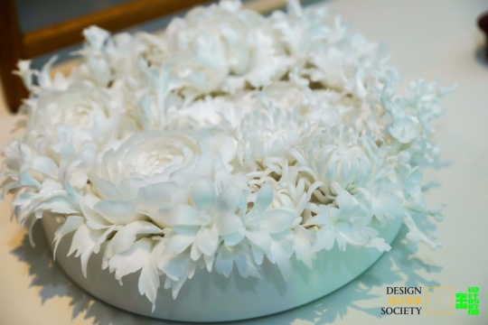 """丁念祖 《花》 2019借展:TING-YING画廊,图片提供:设计互联这是一件在白瓷之都德化烧制的当代瓷器艺术。精美的瓷花被包裹 、收藏在圆柱形器皿中,使这件手工艺品成为一件极致优雅的艺术品,呈现了德华白瓷独有的魅力。福建德化白瓷始于宋元时期,是最早销往欧洲的中国瓷,因其优良的品质被誉为""""中国白""""。"""