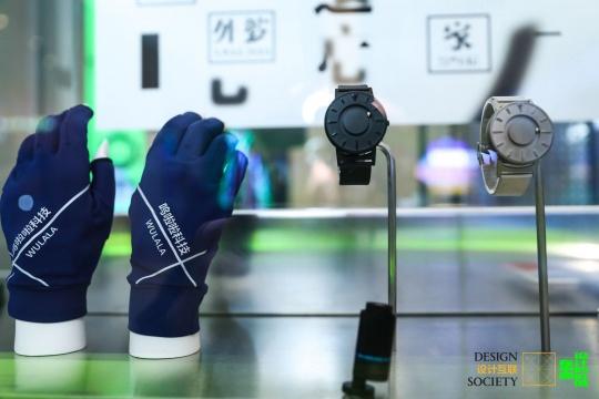 手语翻译手套 设计、借展:呜啦啦科技,图片提供:设计互联  此款手套能够对手语进行实时翻译,帮助聋哑人和普通人沟通。套件包括手套和手机应用。使用者带上手套并下载配套手机应用,就可以将手势的含义实时翻译成文字并播放语音。此应用也可以将语音转译为文字,建立了不同人群沟通的桥梁    触觉设计腕表 设计师:顾力恒,借展方:恒圆贸易(深圳)有限公司,图片提供:设计互联  这款是一款用户可以通过触摸获知时间的手表。它使用钢珠代替指针,表面的钢珠代表分针,表侧的钢珠则是时针,触摸表面滚动的钢珠便可知道时间。即使钢珠离开了指示时间的位置,在磁力的作用下只需轻轻晃动手腕钢珠便可归位。这款手表兼顾了正常人与盲人的使用需求,体现了设计的包容性。